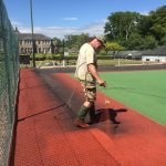 Spraying the first coat of Brick Red onto Tennis CourtSpraying the first coat of Brick Red